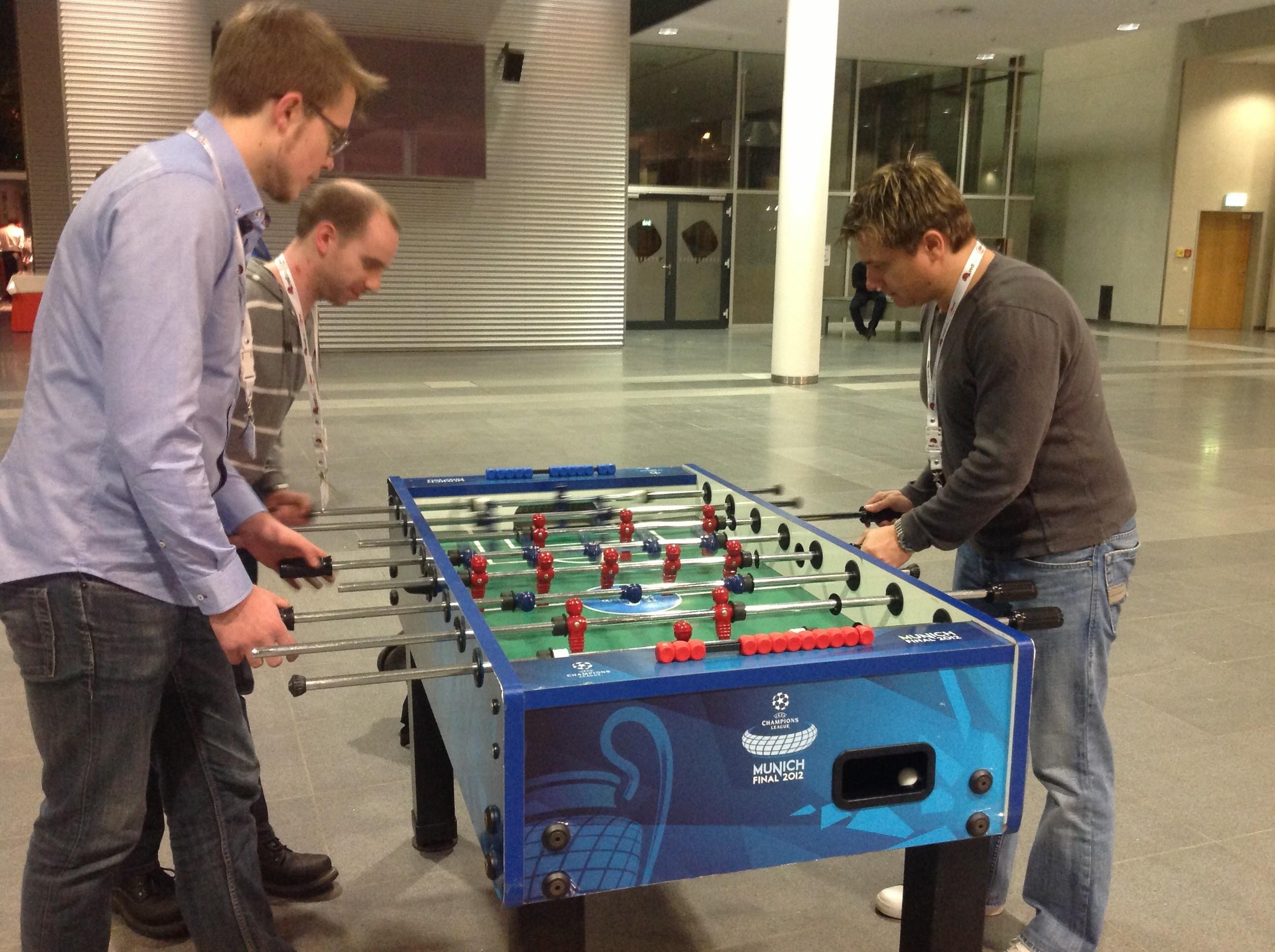 PHP- und Java-Entwickler gemeinsam am Kicker-Tisch.
